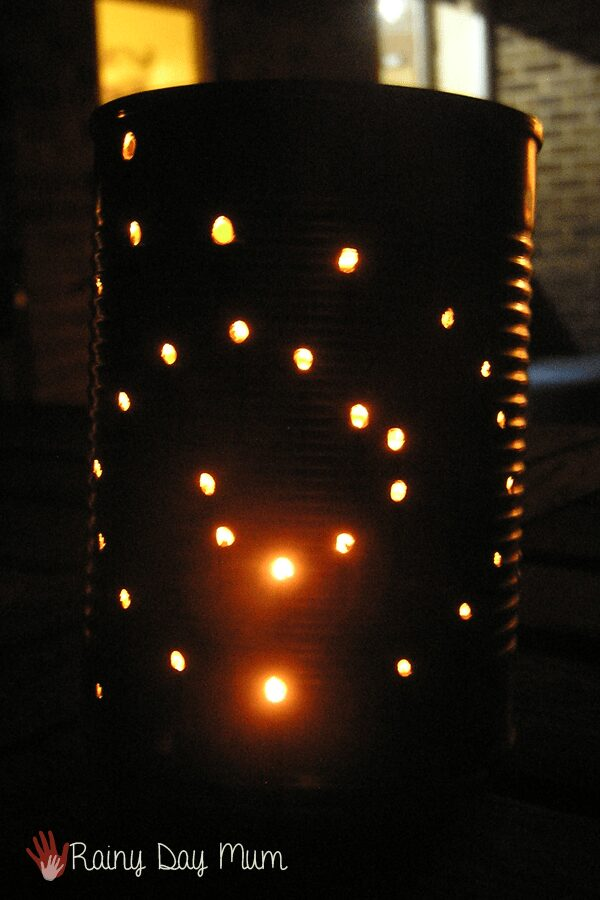 tin can lantern with holes lit up from the inside created by a child