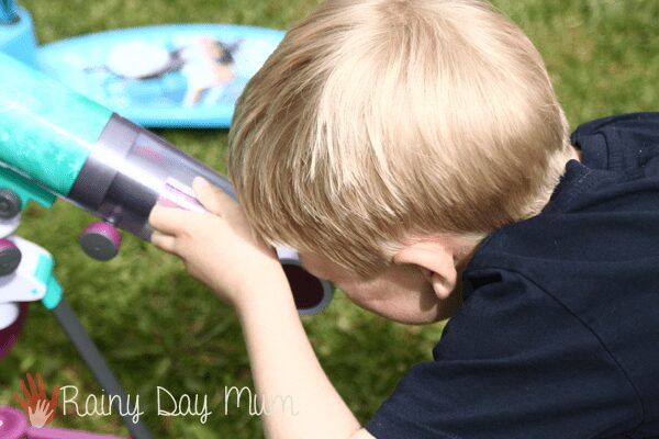 child viewing the day moon through a kids telescope to see the craters great for homeschool science