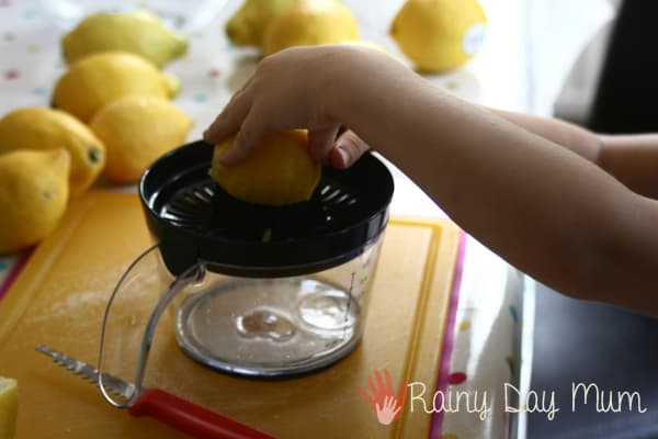 squeezing lemons to make this easy lemonade recipe for kids
