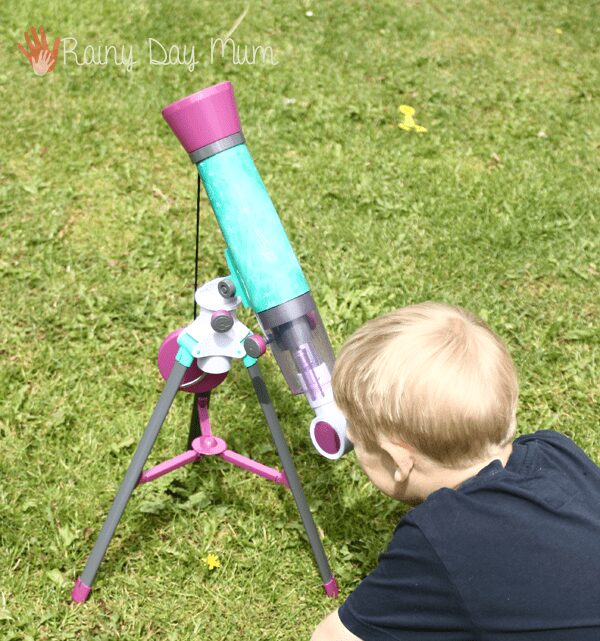 boy using a kids telescope to view birds nests and the moon in the day