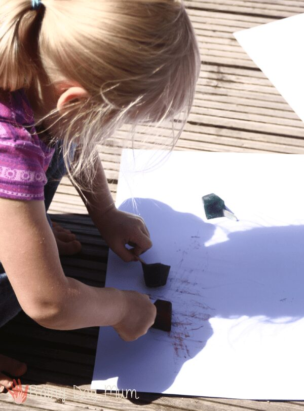 creating pictures with ice paints outside in the summer sunshine