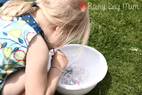 preschool outside blowing through a straw into a bowl to create some bubbles to make a summer art project