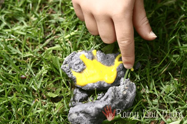 child pointing to the dinosaur toy that they have excavated using vinegar from a baking soda egg fossil