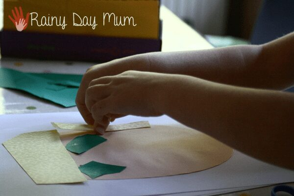 "preschooler gluing ""hair"" from yellow paper to a self portrait collage"