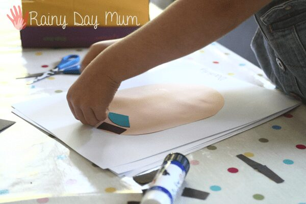 preschooler creating self portraits with paper. Paper shows a round face and adding in blue eyes