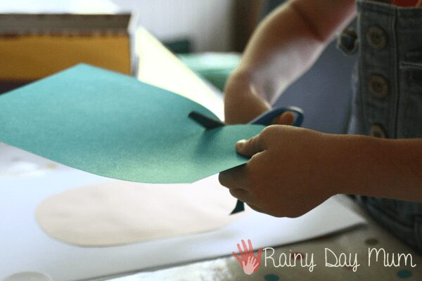 preschooler using scissors to cut paper for a collage