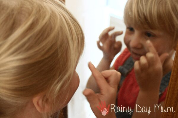 preschooler looking in the mirror pointing to body features to add to a portrait they are making