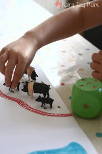 DIY farm themed math activity for preschoolers using a wooden die to add up the number of toy farm animals on the diy math