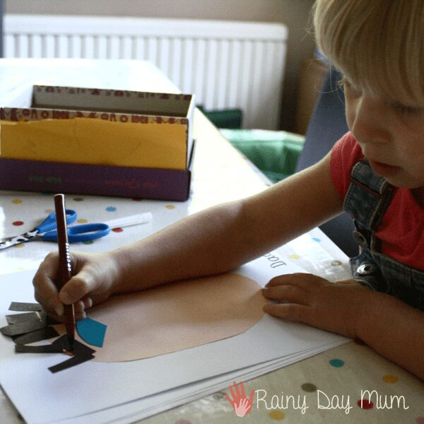 preschooler adding colour with a marker to a portrait of her father