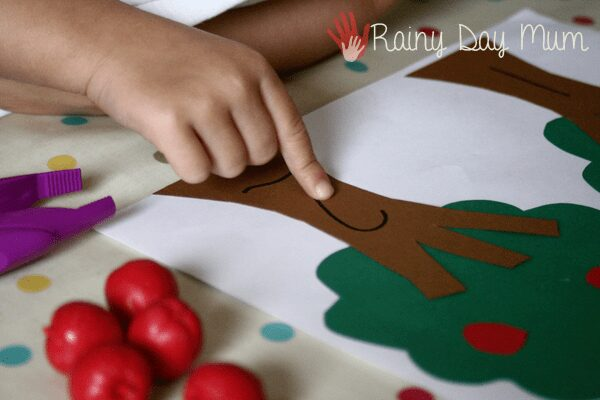 preschooler pointing to the number on the apple tree to match to the apples in the tree