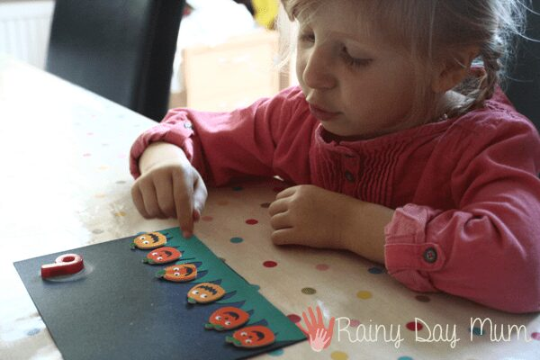 toddler counting pumpkin stickers in a homemade pumpkin book