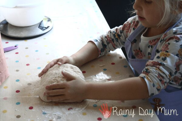 preschooler kneading bread at the kitchen table