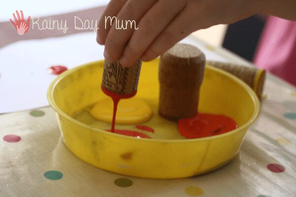 using a cork for printing. a child's hand holding the cork and dipping in red, orange and yellow paint.