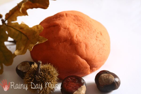 ball of orange playdough with oak leaves and horse and sweet chesnuts around on a white background