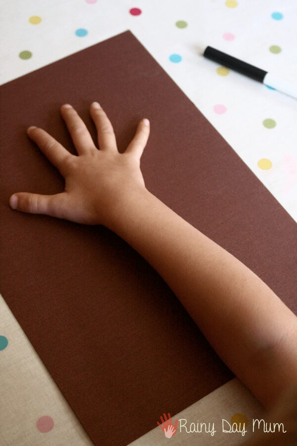 toddler placing hand on brown paper to draw around and create a tree trunk