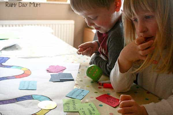 toddler and preschooler sitting playing a handmade rainbow game with movement cards together with mom at the kitchen table