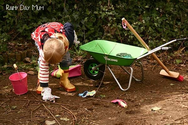 toddler with toddler sized garden equipment