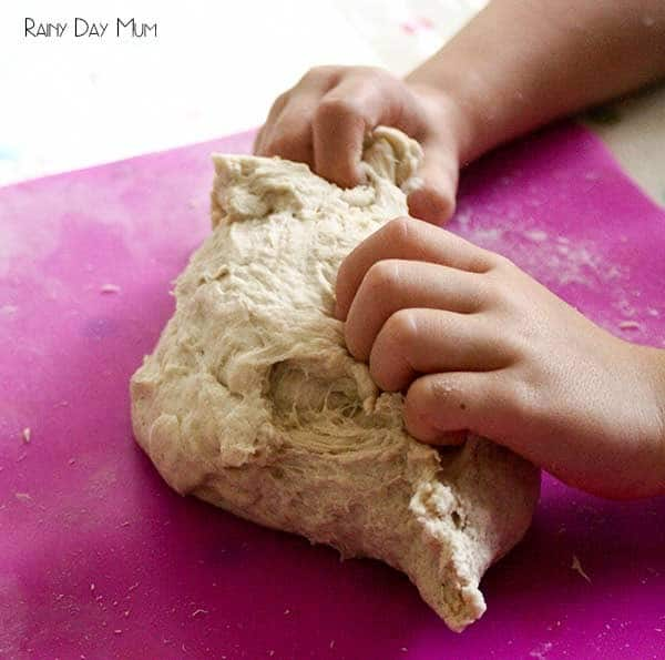 child kneading bread dough on a pink mat