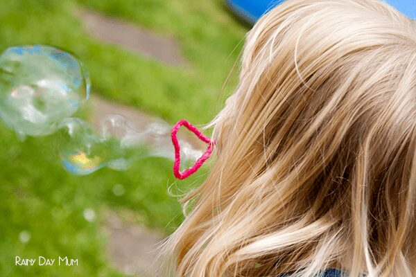 child blowing bubbles with a pipe cleaner bubble wand