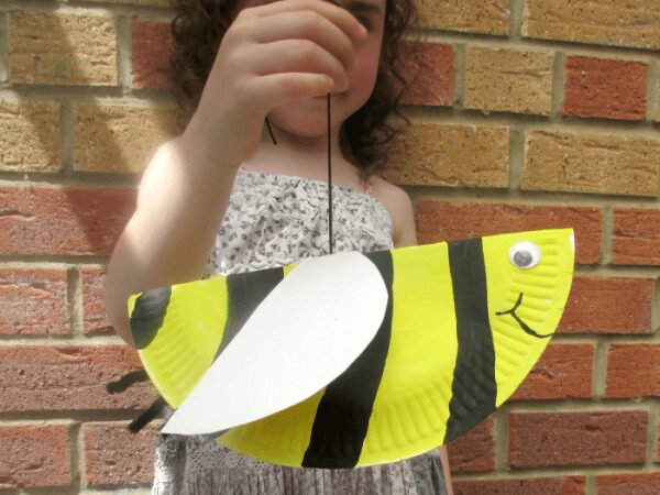 child holding a paper plate bee on a string so that bounces