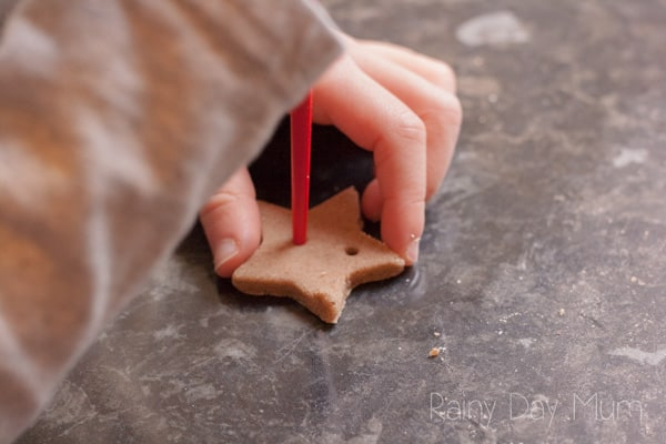 child adding holes to salt dough pre-drying to create a star banner for the Christmas tree