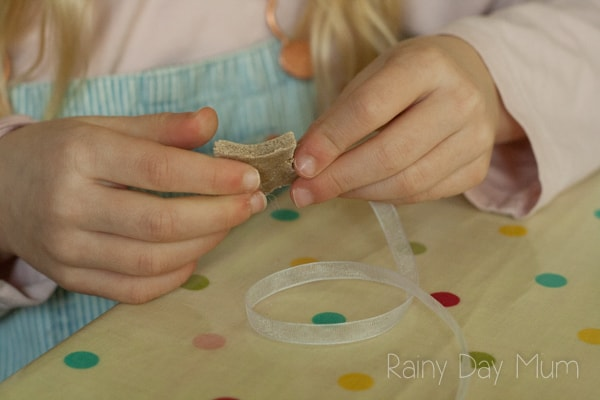 threading salt dough stars with ribbon to create a decorative banner