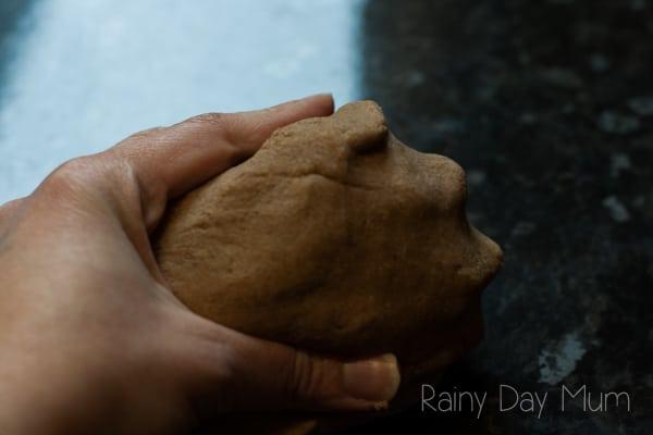 hand holding a ball of gingerbread salt dough on a black surface