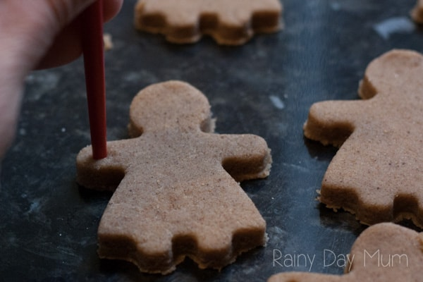 making holes in gingerbread salt dough women to create a garland for Christmas decorations