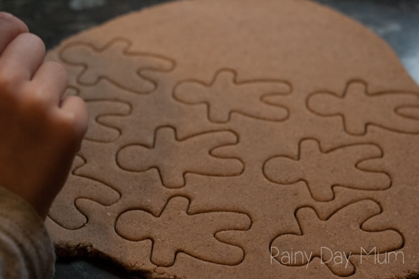 gingerbread salt dough rolled out with cookie cutter gingerbread men pin and child cutting more out