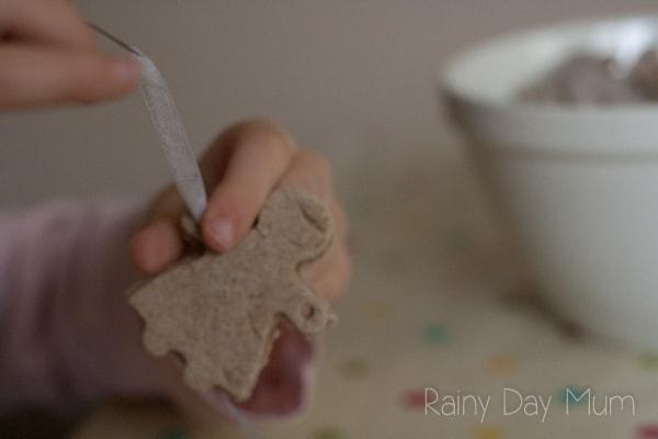 preschooler pulling the ribbon through a gingerbread man salt dough decorations for Christmas