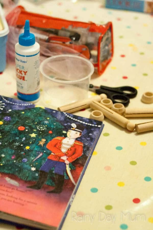 Materials set out to make a Nutcracker Peg Doll with a page from the Nutcracker Book open for inspiration