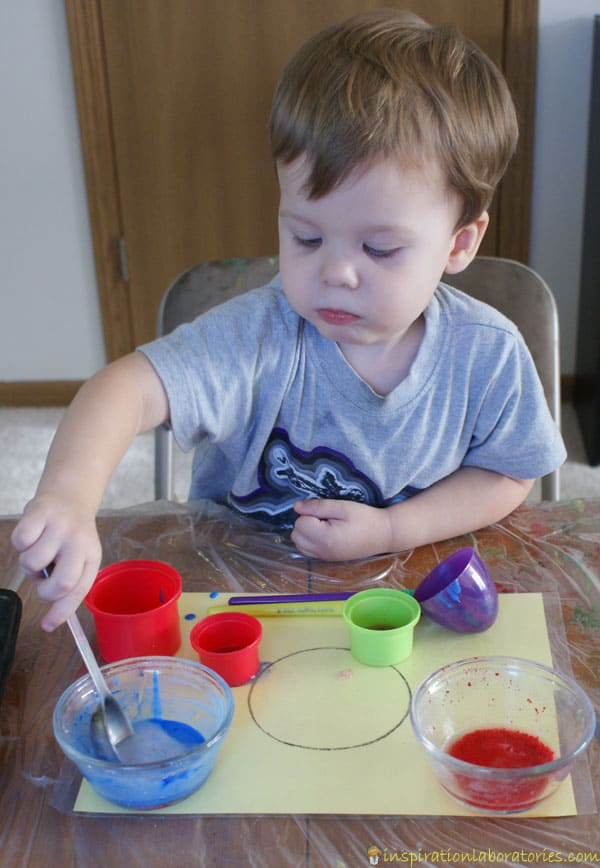 toddler mixing the liquid together in a plastic container