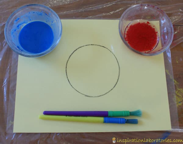 materials set up for painting with baking soda and vinegarm blue baking soda and red vinegar in plastic cups on a yellow piece of paper with a circle drawn and some paint brushes
