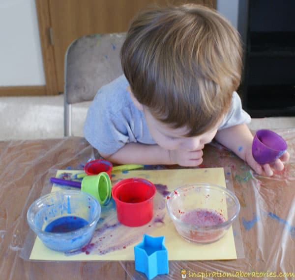 toddler watching the reaction between bicarbonate of soda and vinegar in a cup on the table