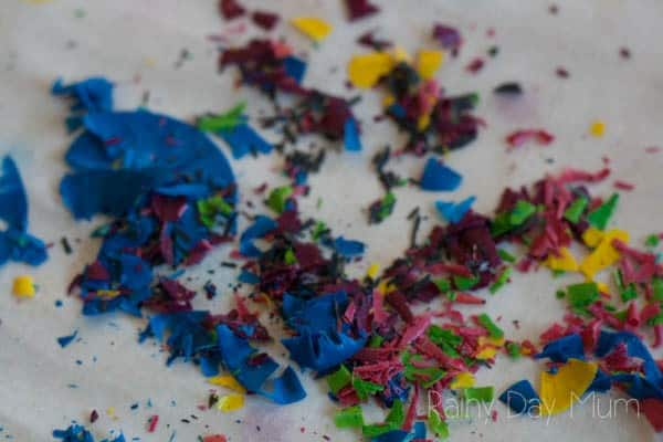 Process Art project for kids using crayons - create beautiful stained glass effect shapes using crayon shavings and scissor skills.
