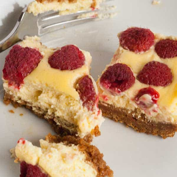 Delicious easy summer dessert recipe for Raspberry and Vanilla Cheesecake Bars with a gingernut crust. Ideal for BBQ's, potlucks and picnics.
