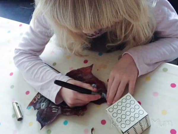 preschooler decorating a leaf copying the patterns on the leaf from a diy dice