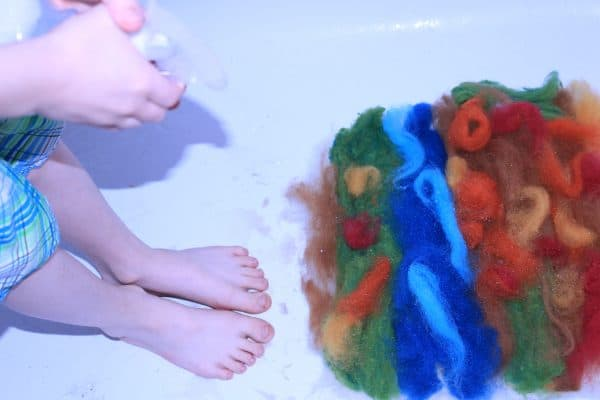 spraying the wool to create a wet felted play mat for kids nature tables