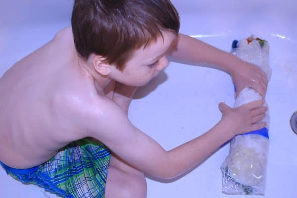 child rolling a wet felted playmat in the bath