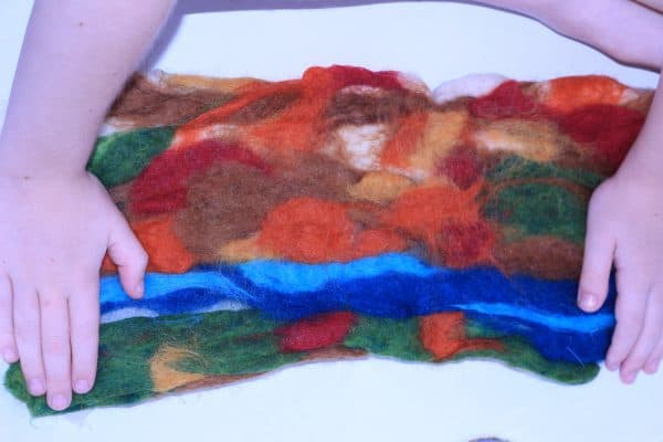 layers of wool roving revealed for a small nature table play mat surface to make with kids