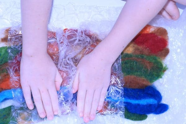 wet felting with kids - using wool roving and bubble wrap to create a play mat for the nature table