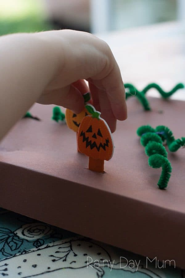 preschoolers hand picking pumpkins from a DIY pumpkin patch game for learning