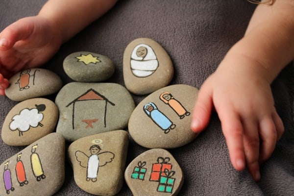 child's hands going to play with the nativity story stones