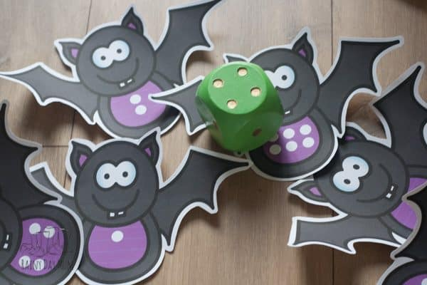 bat themed maths game for halloween to play with preschoolers matching the spots on the dice to the spots on the bat to work on recognition of numbers in patterns
