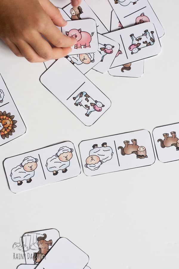 kids playing with a printed domino farm animal game from rainy day mum