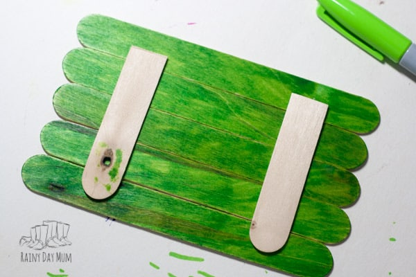 Easy Popsicle Stick Craft for toddlers and preschoolers to create a Grinch perfect for some book or movie inspired creativity leading up to Christmas.