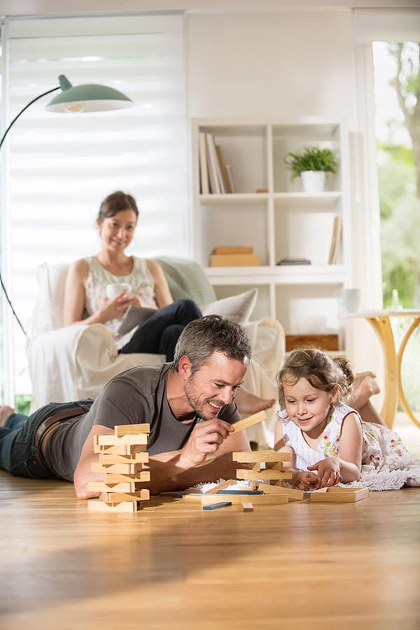 dad playing jenga with daughter as mum looks on