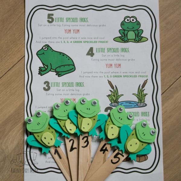 words to the nursery rhyme 5 little speckled frogs printed with the craft foam puppets for circle time laid on the top