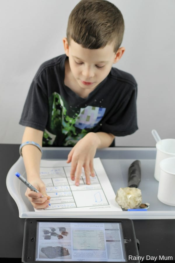 child filling in a rock type identification sheet whilst observing rocks