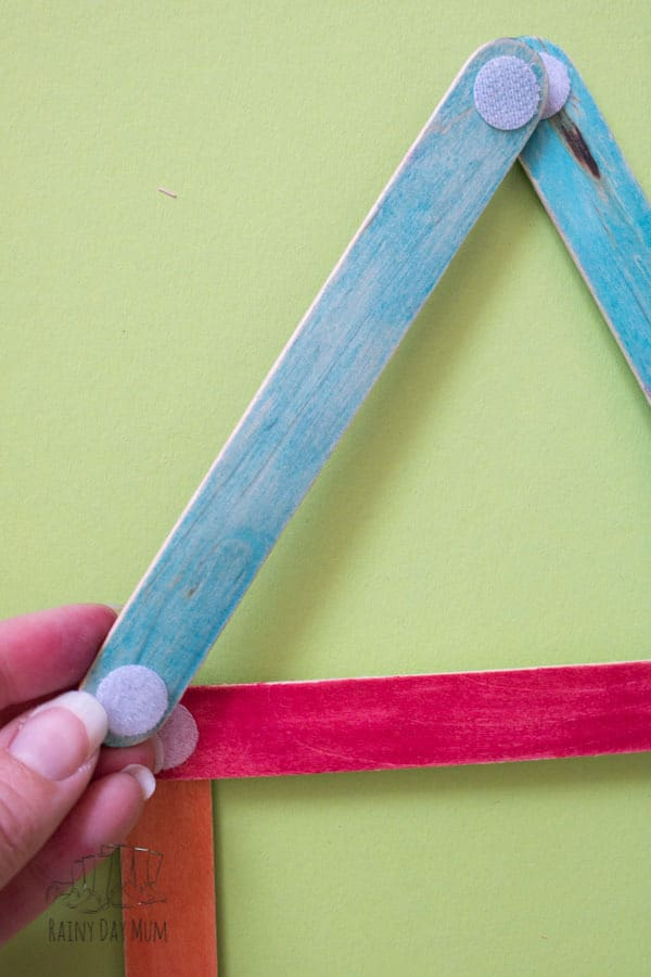 Simple shape activity for toddlers and preschoolers inspired by the classic fairy tale Three Little Pigs using craft sticks to make shape and colour houses.